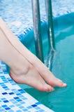Vrouwelijke benen in het poolwater Stock Foto's