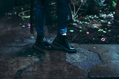 Vrouwelijke benen in hoge laarzen van verf op de achtergrond, nat beton, manierschoenen royalty-vrije stock afbeeldingen