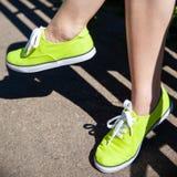 Vrouwelijke benen in lichtgroene tennisschoenen royalty-vrije stock afbeelding