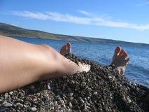 Vrouwelijke benen op het strand Stock Afbeeldingen