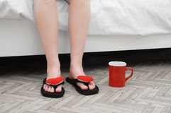 Vrouwelijke benen in pantoffels en een rode mok op de vloer Het zitten op het bed binnen ruimte stock afbeeldingen