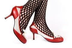 Vrouwelijke benen in rode schoenen Stock Fotografie