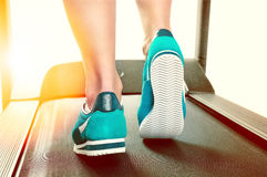 Vrouwelijke benen in turkooise tennisschoenen op een tredmolen Stock Foto