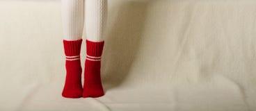 Vrouwelijke benen in warme witte gebreide legging en rode sokken op whit stock fotografie