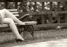 Vrouwelijke benen in zwarte sandals in de zomer, op de bank royalty-vrije stock afbeelding
