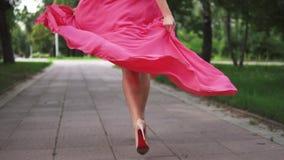 Vrouwelijke benenclose-up het meisje in de rode kleding en de schoenen op hoge hielen loopt bij de groene steeg in Park weg langz stock footage