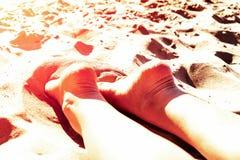 Vrouwelijke benenhielen omhoog op een zandig strand in een Sunny Tropical-vakantieconcept vakantie en ontspanningspekudei de zon Stock Fotografie