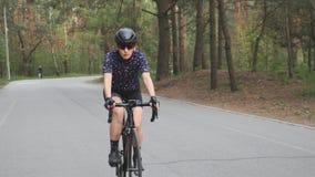 Vrouwelijke berijdende fiets in het park Het cirkelen opleiding De voorzijde volgt schot Geschiktheid op fiets stock video
