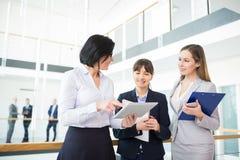 Vrouwelijke Beroeps die over Tabletcomputer met Colleag bespreken stock afbeelding