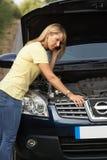 Vrouwelijke Bestuurder die bij de Landweg wordt opgesplitst Stock Foto's