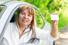 Vrouwelijke bestuurder die een lege kaart tonen stock foto