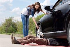 Vrouwelijke bestuurder die een werktuigkundige op haar auto bijstaan stock foto's
