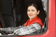 Vrouwelijke bestuurder die uit vrachtwagen kijken Stock Foto