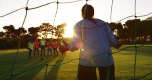 Vrouwelijke bewaarder die de bal in doel op voetbalgebied tegenhouden 4K stock video