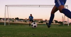 Vrouwelijke bewaarder die op vrouwelijke voetballer wachten om de bal te schieten 4K stock footage