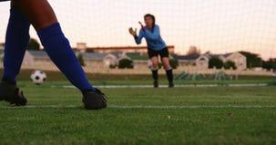 Vrouwelijke bewaarder die op vrouwelijke voetballer wachten om de bal te schoppen 4K stock videobeelden