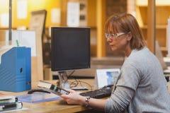 Vrouwelijke bibliothecaris die een boek houden die de dekking lezen royalty-vrije stock foto
