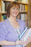 Vrouwelijke bibliothecaris die houdend sommige boeken stellen stock afbeelding