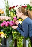 Vrouwelijke bloemist in bloemwinkel Stock Foto's