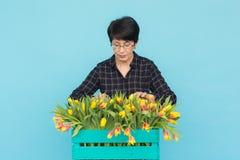Vrouwelijke bloemist die op middelbare leeftijd blauwe houten doos van tulpen in studio houden stock afbeelding