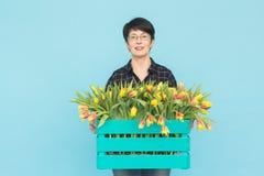 Vrouwelijke bloemist die op middelbare leeftijd blauwe houten doos van tulpen in studio houden royalty-vrije stock fotografie
