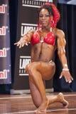 Vrouwelijke bodybuilder die in rode bikini op stadium presteren Royalty-vrije Stock Afbeeldingen