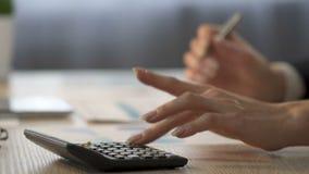 Vrouwelijke boekhouder gebruikend calculator en neerschrijvend gegevens over grafiek, zaken stock footage