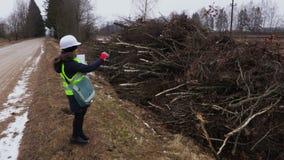Vrouwelijke bosbouwinspecteur die dichtbij het felling van struiken schrijven stock videobeelden