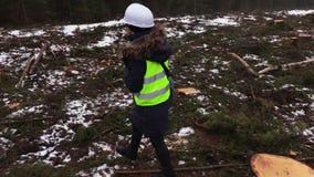 Vrouwelijke bosbouwinspecteur die vernietigd bos inspecteren stock footage
