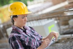 Vrouwelijke bouw die klembord controleren stock afbeelding