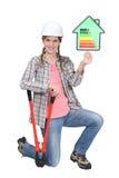 Vrouwelijke bouwer die energieteken toont Stock Afbeeldingen