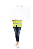 Vrouwelijke bouwer die lege banner houden en haar gezicht behandelen Stock Foto's