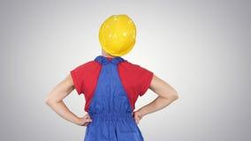 Vrouwelijke bouwvakker die met handen op heupen iets op gradiëntachtergrond bekijken stock video