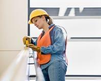 Vrouwelijke bouwvakker die meting neemt stock foto