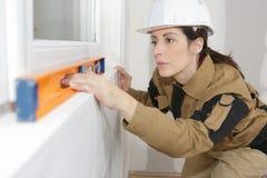 Vrouwelijke bouwvakker die vensters installeren royalty-vrije stock fotografie