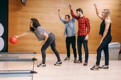 Vrouwelijke bowlingspeler die op steeg, bal in actie werpen royalty-vrije stock afbeelding