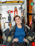 Vrouwelijke Brandbestrijder Standing Against Firetruck bij Royalty-vrije Stock Foto's
