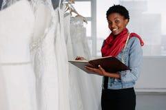 Vrouwelijke bruids slijtageontwerper die in boutique werken stock foto