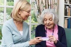 Vrouwelijke Buur die Hogere Vrouw met Medicijn helpen royalty-vrije stock foto's