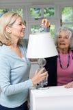 Vrouwelijke Buur die Hogere Vrouwenverandering Lightbulb in Lamp bevorderen stock foto
