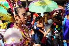 Vrouwelijke Carnaval-danser in etnische kostuumsgrimassen onder zonhitte stock fotografie