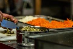 Vrouwelijke Chef-kok Chopping Pickled Cucumbers voor Salades, Huwelijksmaaltijd royalty-vrije stock foto