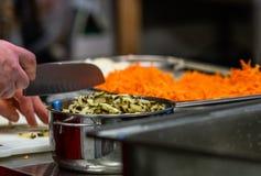 Vrouwelijke Chef-kok Chopping Pickled Cucumbers voor Salades, Huwelijksmaaltijd stock fotografie