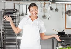 Vrouwelijke Chef-kok Gesturing In Kitchen Stock Foto