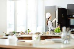 Vrouwelijke chef-kok in hoed het openen ijskast stock afbeelding