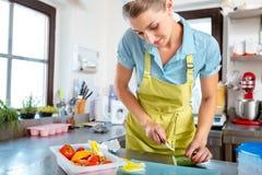 Vrouwelijke chef-kok scherpe komkommer met mes stock afbeeldingen