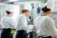 Vrouwelijke Chef-koks die in industriële keuken werken royalty-vrije stock afbeeldingen