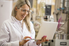 Vrouwelijke chemicus die met laptop computer in het laboratorium werken Royalty-vrije Stock Fotografie