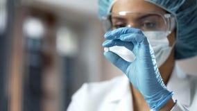 Vrouwelijke chemicus die witte pil, het nieuwe medicijn testen in laboratorium bekijken royalty-vrije stock afbeelding
