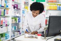 Vrouwelijke Chemicus Writing On Clipboard bij Teller stock afbeeldingen